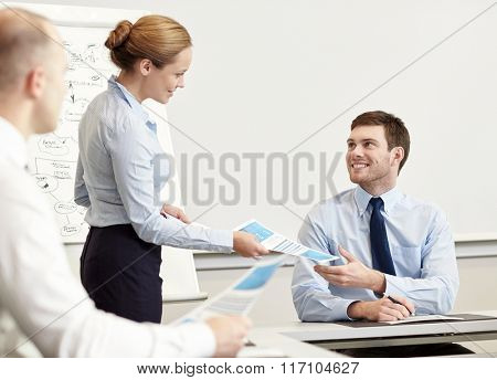 smiling woman giving papers to man in office