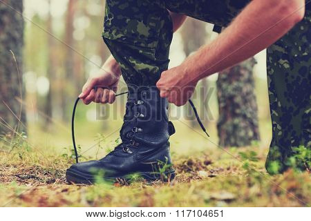 close up of soldier tying bootlaces in forest