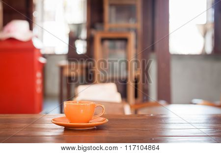 Orange Coffee Cup On Wooden Table