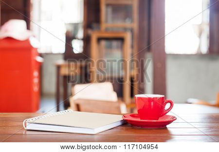 Red Coffee Cup With Notebook On Wooden Table