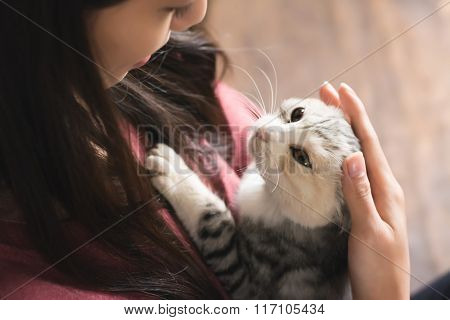 An Asian woman play with her kitten at home.