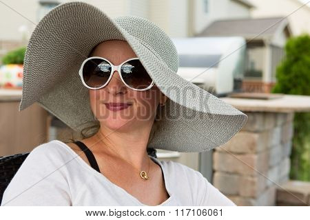 Woman In Hat And Sunglasses Sitting On Back Patio