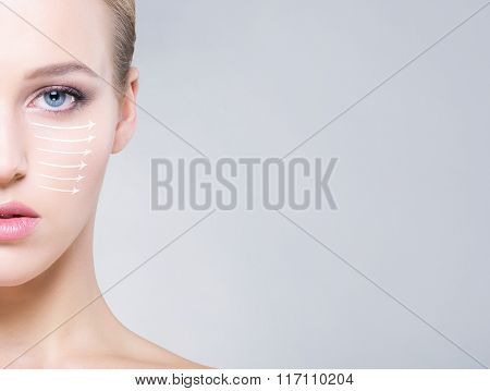 Half face portrait of beautiful, healthy woman over grey background. Face lifting concept.
