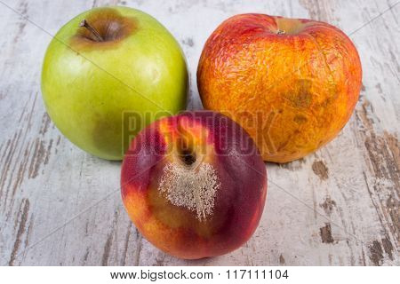 Spoiled Peach And Apple On Old Wooden White Table