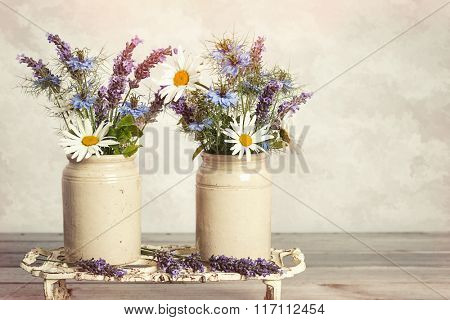 Lavender and daisies in ceramic pots on rustic wooden table