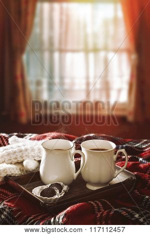 Hot chocolate drinks on tartan rug with winter sunshine filtering through the window
