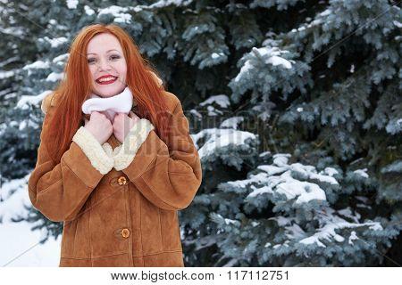 Winter redhead woman outdoor portrait, snowy fir trees background