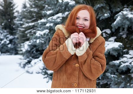 Winter redhead woman outdoor portrait, snowy fir trees background