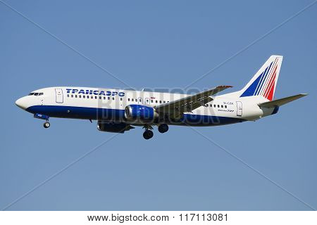 Flying the Boeing 737-400 (EI-CZK) company Transaero Airlines on the background of blue sky