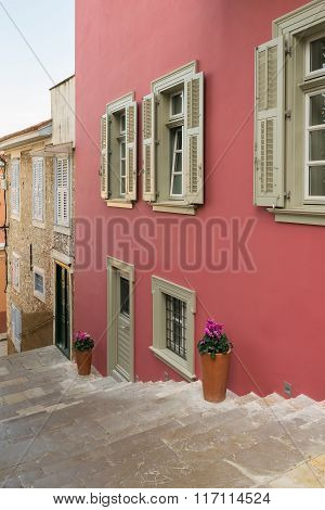 Traditional alley at Nafplio in Greece with pink walls and flowers.