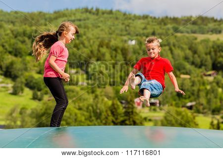 Children Bouncing Up And Down On Trampoline