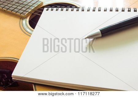 Notebook And Pen On Guitar