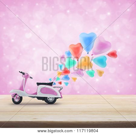 Pink Scooter Toy With Colorful Heart Love Balloon On Wooden Table Over Pink Heart Bokeh Background,