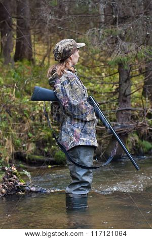 Woman Hunter Looking Out For Prey On Small River In The Forest