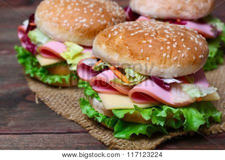 Burger sandwich with sausage, cheese and vegetables on a wooden background