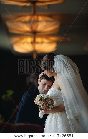 Bride With A Bouquet In Hands Gently Embraces The Groom