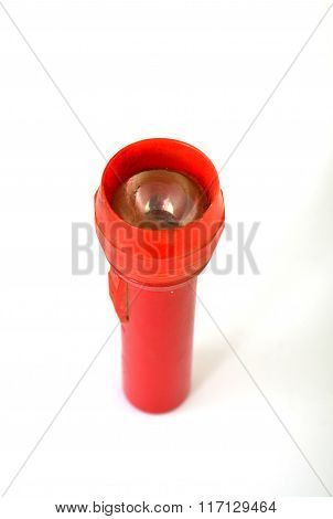 Picture of a Vintage red dirty flashlight on white