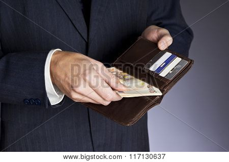 Businessman hands holding wallet with credit cards and stack of money