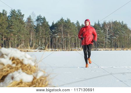 Well built running man outdoors in winter snowy forest