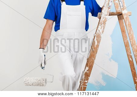 Painter With Paint Roller On Ladder