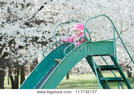 Little smiling girl in pink jacket sliding down old playground slide at fruit tree white blossom bac