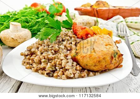 Cutlets of turkey with buckwheat and mushrooms in plate on board