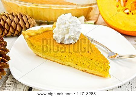 Pie pumpkin in plate with cream on light board