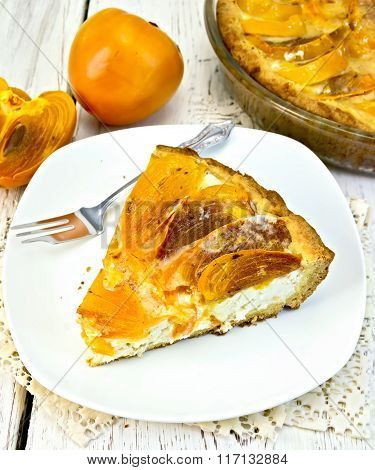 Pie with curd and persimmons in plate on napkin silicone