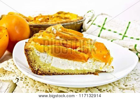Pie with curd and persimmons in plate on napkin