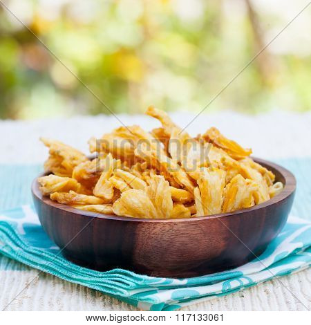 Dried dehydrated deep fried pineapple chips in a wooden bowl on a textile background