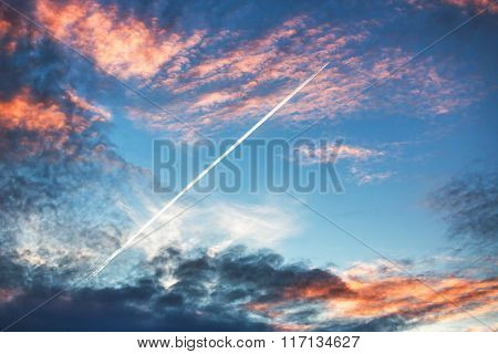 Airplane Flies In Sunset Dramatic Clouds And Leaving Trail