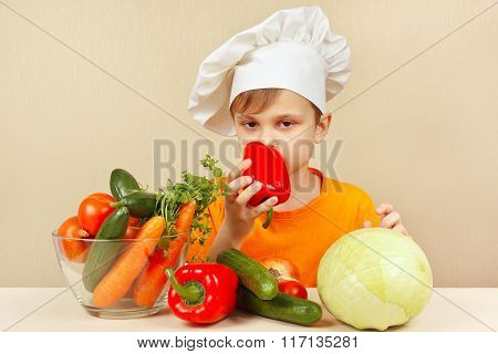 Little boy in chefs hat chooses fresh vegetables for salad at table