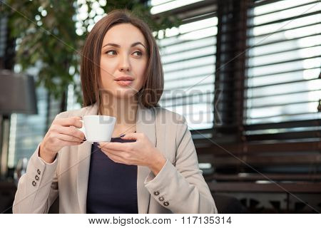 Pretty young woman is enjoying hot drink
