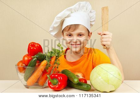 Little boy in chefs hat with fresh vegetables at table