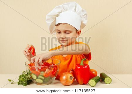 Little boy in chefs hat puts chopped vegetables for salad in a bowl