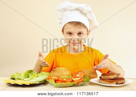 Little funny chef at the table with ingredients for hamburger
