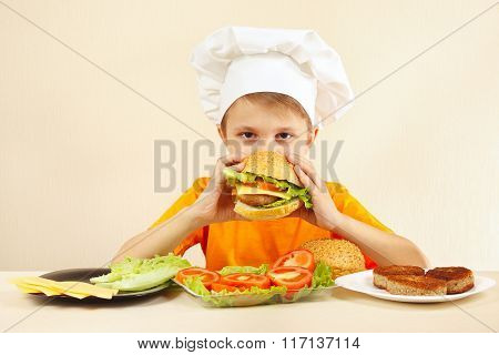 Little funny chef is tasting cooked hamburger