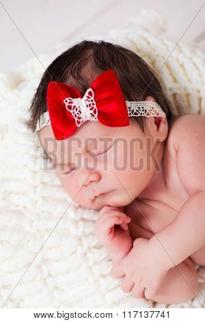 Portrait Of Little Newborn Baby Girl With A Red Bow On Her Head. Sleeping Kid.concept Of Holiday Gre