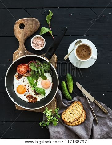 Breakfast set. Pan of fried eggs, bacon, tomatoes with bread, mangold and cucumbers, coffee on rusti
