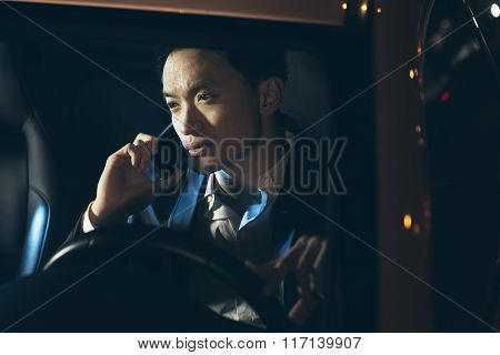 Young Asian Businessman Calling With Cellphone In Car At Night.