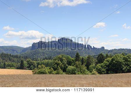 Group Of Rocks Schrammsteine And Falkenstein With Grain Field And Blue Sky In Saxon Switzerland