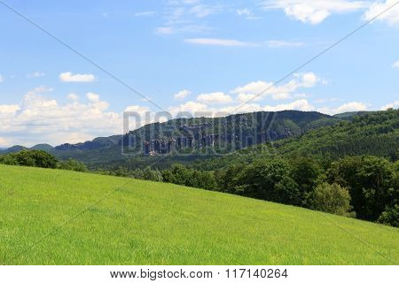 Group Of Rocks Affensteine With Meadow And Blue Sky In Saxon Switzerland
