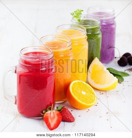Smoothies, juices, beverages, drinks variety with fresh fruits and berries on a white wooden backgro