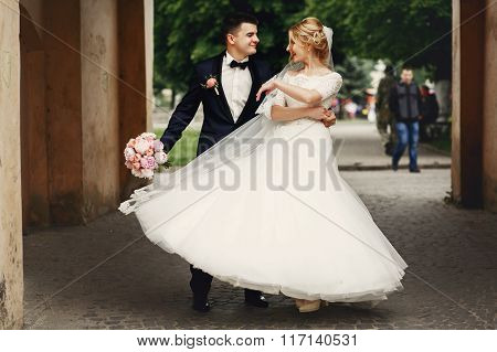 Happy Handsome Groom And Blonde Beautiful Bride In White Dress Dancing Under Arc