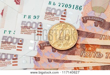 American Dollar Coin Over Russian Banknotes Close Up