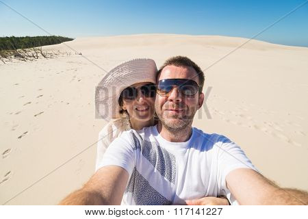 Couple Taking Selfie With Sand And Sky In Background