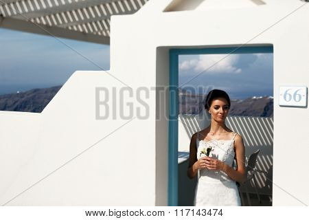 Elegant Brunette Bride In White Dress Posing Near Doorway With Bouquet