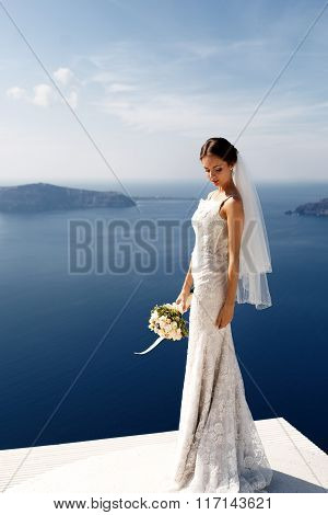 Romantic Beautiful Bride In White Dress Posing On Terrace With Sea And Mountains In Background