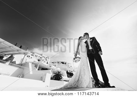 Romantic Beautiful Couple Kissing On Terrace With Sea, Islands And Mountains In Background B&w