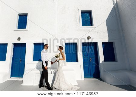 Handsome Confident Groom And Beautiful Caucasian Bride Posing Near White Wall With Blue Windows